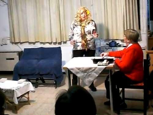 Autora: Esther Kershenovich  Actores: Petty Kleinman -- Esther Kershenovich. Para leer más sobre nuestra colaboradora Esther Kershenovich, oprima aquí. Entra Estrella -una borracha- a una oficina, ahí está sentada Sara -una secretaria solterona-, vestida muy recatadamente y con lentes. ESTRELLA: Hola señora. SARA: Señorita por favor, ¿en qué puedo servirla? ESTRELLA: Sírvemela con mucho hielo, en las rocas. SARA: ¿De qué me habla? ESTRELLA: Señora, perdón señorita, dígame ¿acá es AA? SARA: No, aquí es A.M. ESTRELLA: ¿A. M.? Pero si ya es P.M. SARA: Aquí es A.M. Agencia Matrimonial ESTRELLA: ¿Agencia matrimonial? Entonces me equivoqué, yo busco los 12 pasos que me van a llevar a la felicidad. (Se levanta para irse) SARA LA TRAE DE REGRESO GRITANDOLE: Venga, venga escúcheme yo también la puedo acercar a la felicidad incluso en dos pasos. ESTRELLA: ¿Usted haría eso por mí? SARA: Por supuesto, usted tiene que darme 2 cheques de 5ooo pesos y yo le entrego la felicidad. ESTRELLA: JA JA, esto me esta gustando, ¿dos pasitos así chiquitos? ¿O así? (Y empieza a cantar y bailar salsa) SARA: Por favor, tranquilita, mejor siéntese y dígame que quiere, ¿qué le gusta? ESTRELLA: Quiero beber… SARA: Así que le gustan los bebes…. (REVISANDO LAS FOTOS) ESTRELLA: Si bebe… SARA: Mire no tengo exactamente bebes pero estos jovencitos están muy bien, que importa si ya están rozando los cincuentas. ESTRELLA: MMMMMM no están nada mal, aunque algo caro, ¿no cree? Y dígame ¿ellos me pueden acompañar al paraíso?  SARA: Al paraíso no se, pero a lo mejor al altar. ESTRELLA: Es que en el paraíso me están esperando ya que ahí voy todas las noches. SARA: ¿Usted va al paraíso todas las noches? ESTRELLA: Si, y ahí me dan una mezcla del rojo, del blanco y del amarillo que me hace olvidar quien soy y a donde voy…Y vuelo y vuelo. SARA: Mire estos jóvenes a lo mejor la llevan al paraíso, pero no se de que rojo o blanco en fin de que arco iris me esta hablando. ESTRELLA: De Iris, de mi prima Iris, la que m